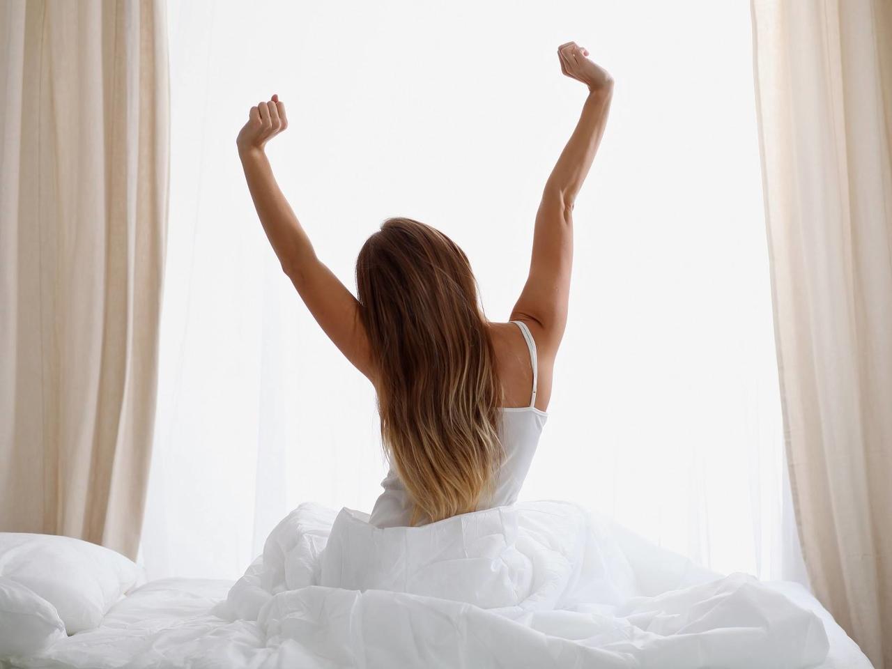 uykusundan uyanıp gerinen kadının sırtı, güzellik uykusundan uyanan uzun saçlı kadın