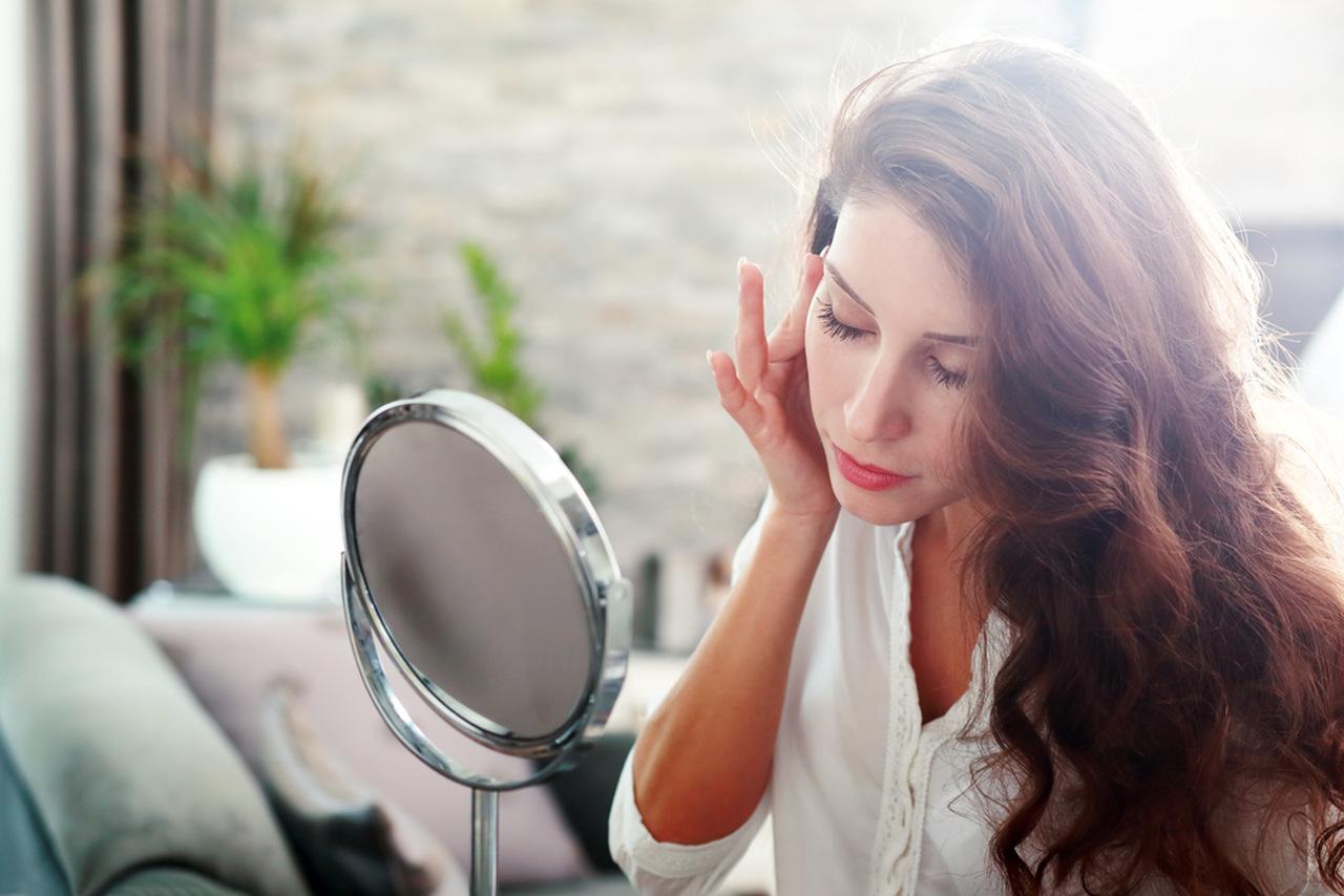ayna karşısında cildini inceleyen uzun saçlı kadın, normal ciltler için cilt bakımı