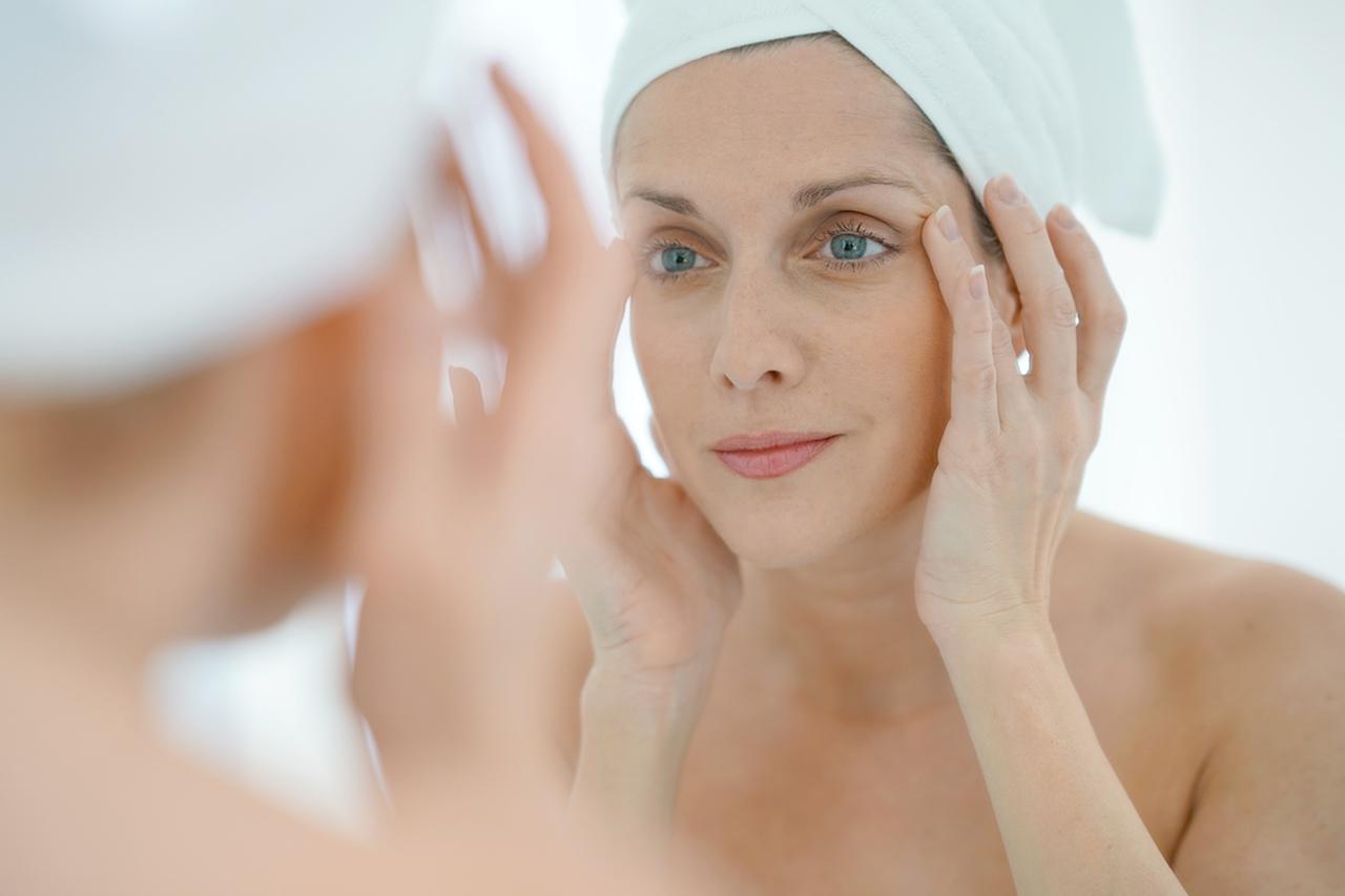 aynada cildini inceleyen orta yaşta kadın, olgun ciltler için cilt bakımı