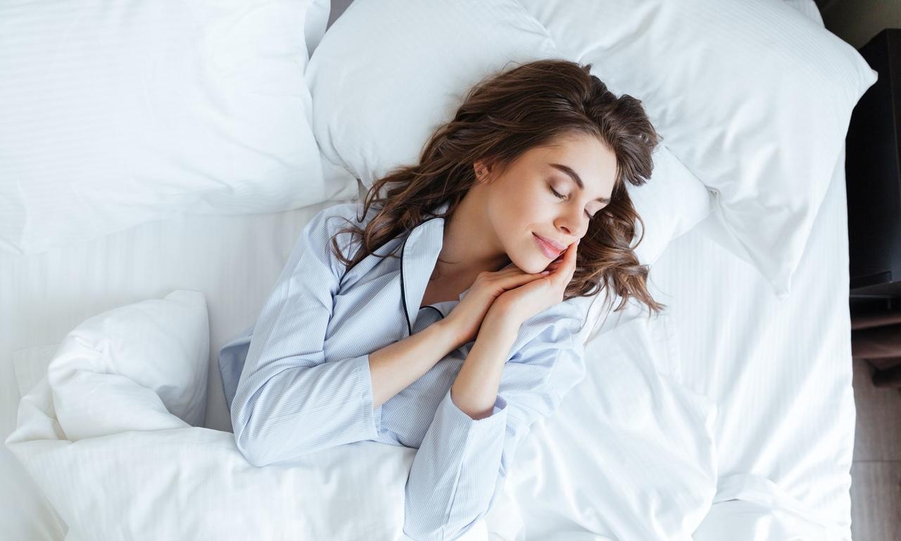 beyaz nevresim içinde sırtüstü uzanarak uyuyan uzun saçlı güzel kadın