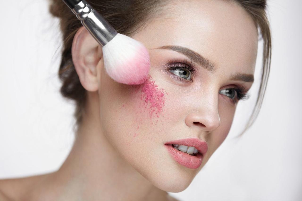 makyaj malzemeleri isimleri arasında en tanınmış olan allığı fırça yardımıyla yanağına süren kadın