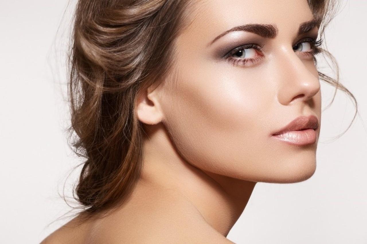 aydınlatıcı kullanarak yüzünün bazı bölümlerini ön plana çıkaran makyajlı ve bakımlı kadın