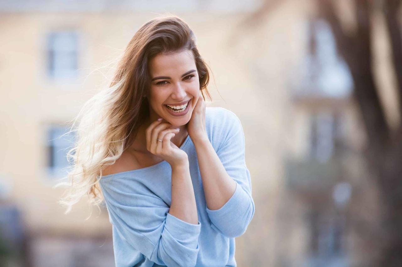 sokakta yürürken gülerek poz veren uzun saçlı ve mavi bluzlu kadın