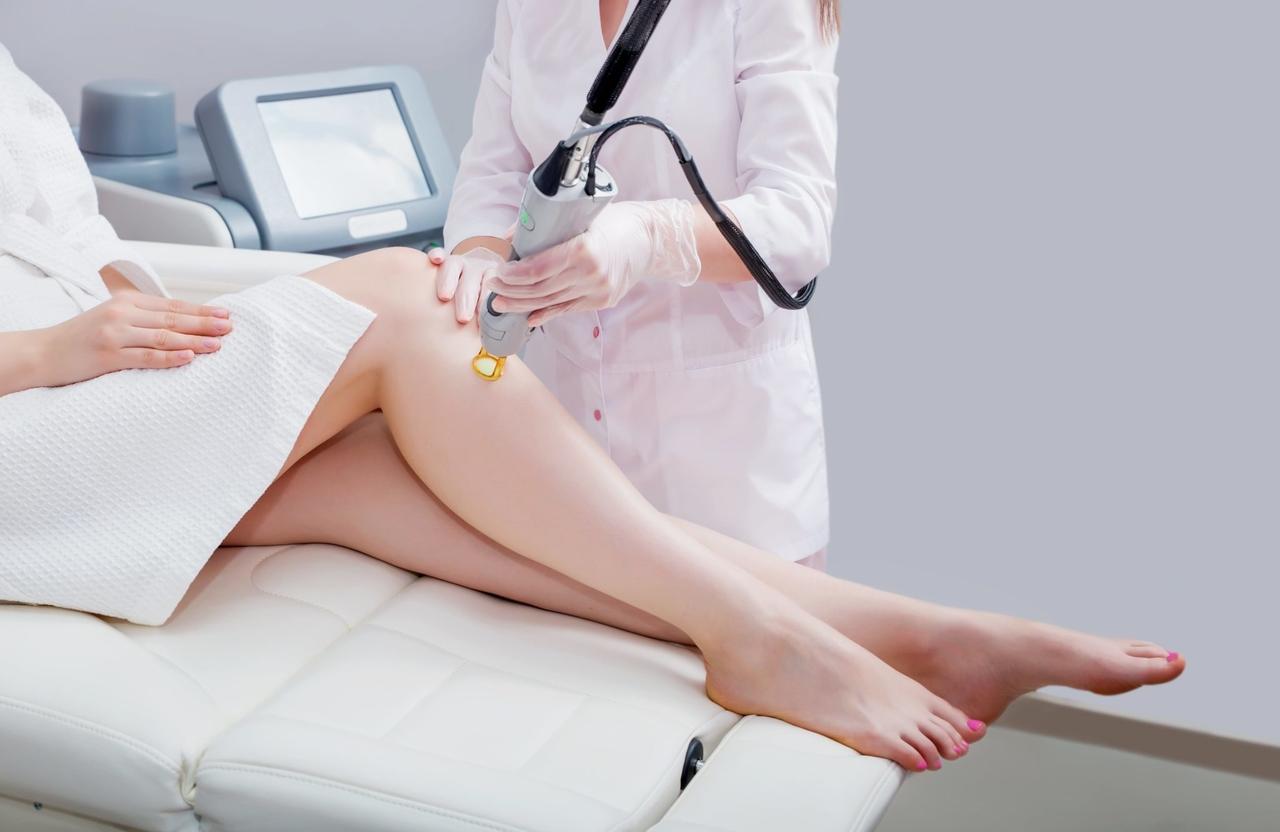 güzellik merkezinde güzellik uzmanına lazer epilasyon yaptıran bornozlu kadın