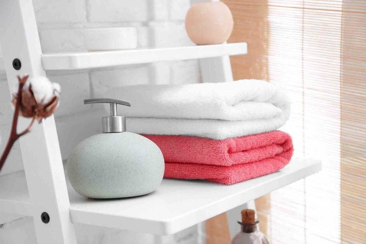 sıvı sabun ile birlikte rafta duran pembe ve beyaz renkte katlanmış havlular