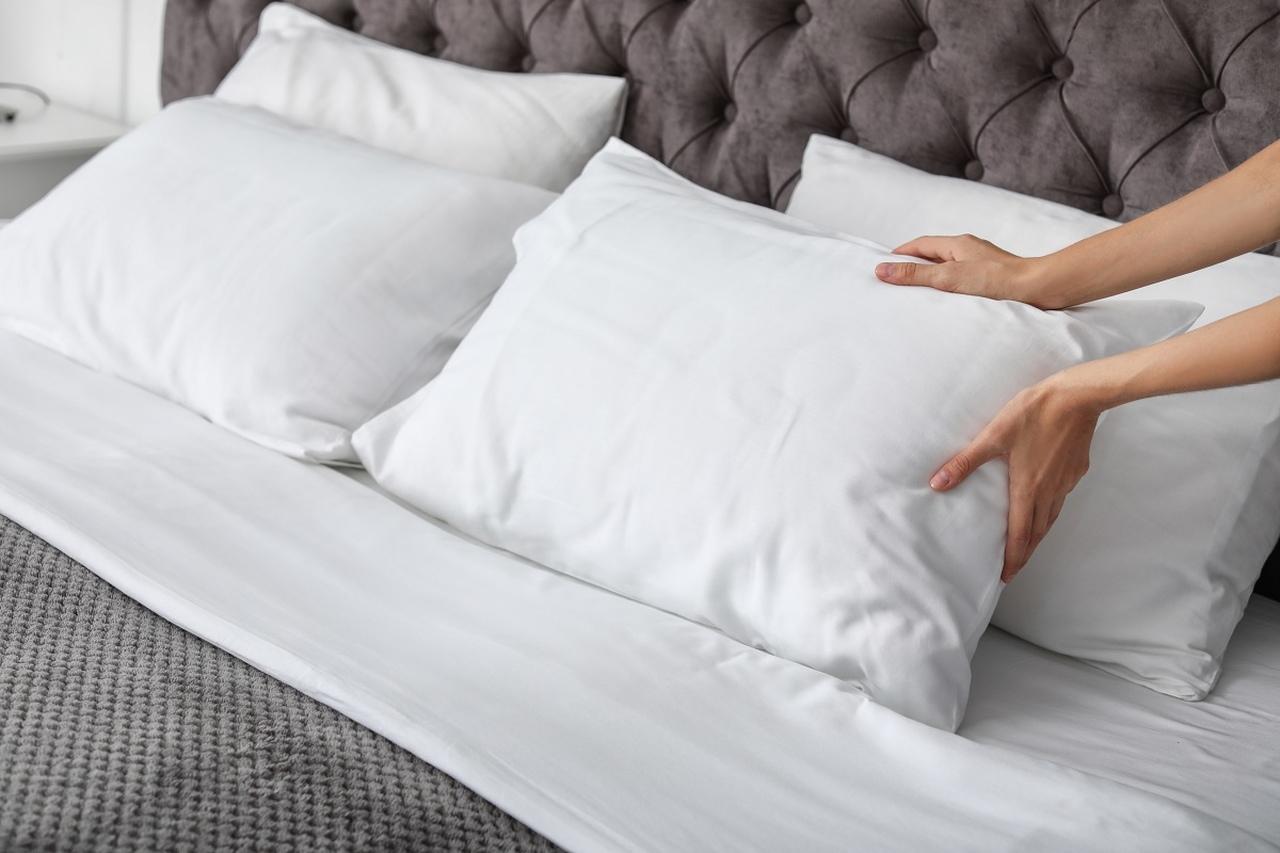 çift kişilik yatakta yastıkları düzelten kadın eli