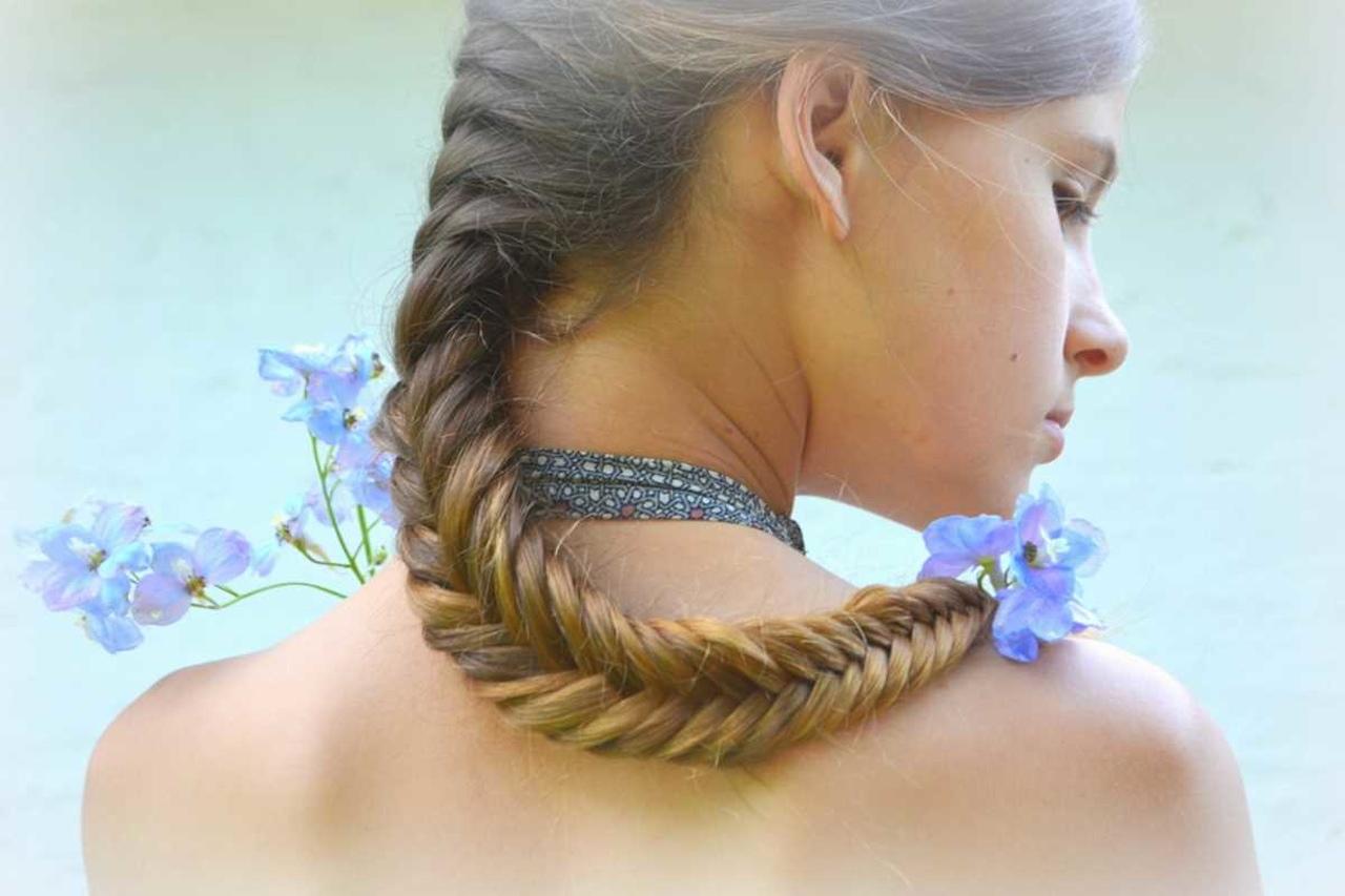 Balıksırtı örgü saçlarının ucuna çiçek takmış kadının arkadan görünümü
