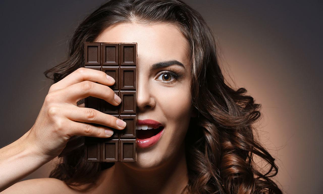 Göz hizasında bitter çikolata tutan mutlu kadın