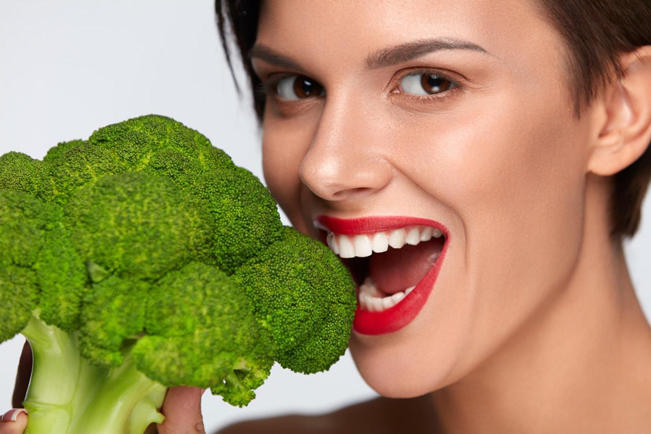 Elinde tuttuğu brokoliyi yiyecekmiş gibi duran kırmızı rujlu kadın