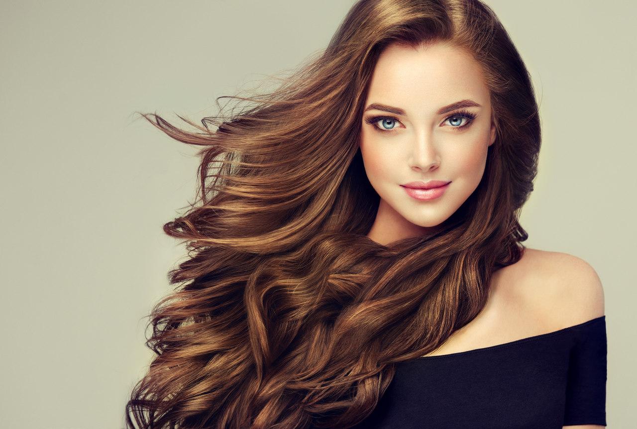 Dalgalı uzun saçlara sahip gülümseyen kadın