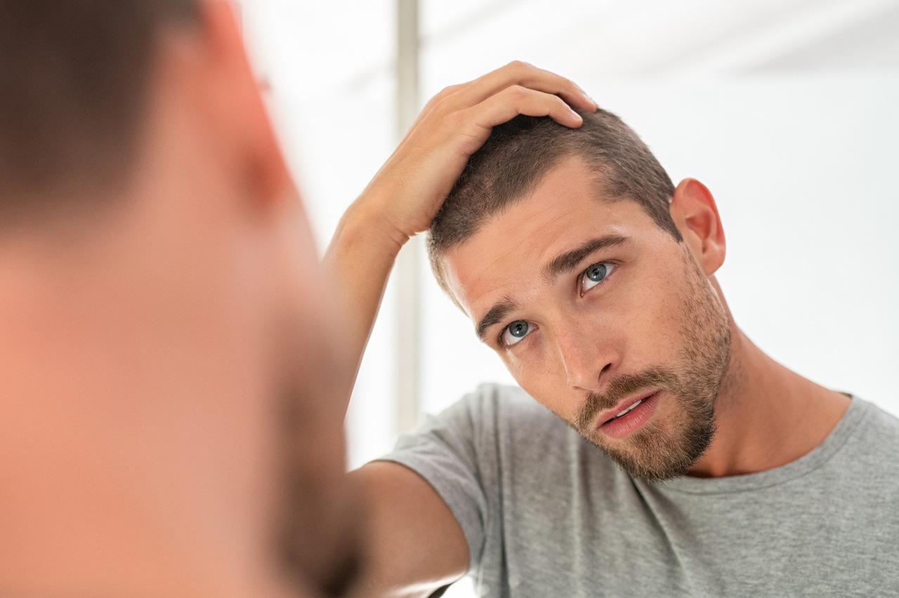 Ayna karşısında seyrekleşen saçlarını inceleyen adam