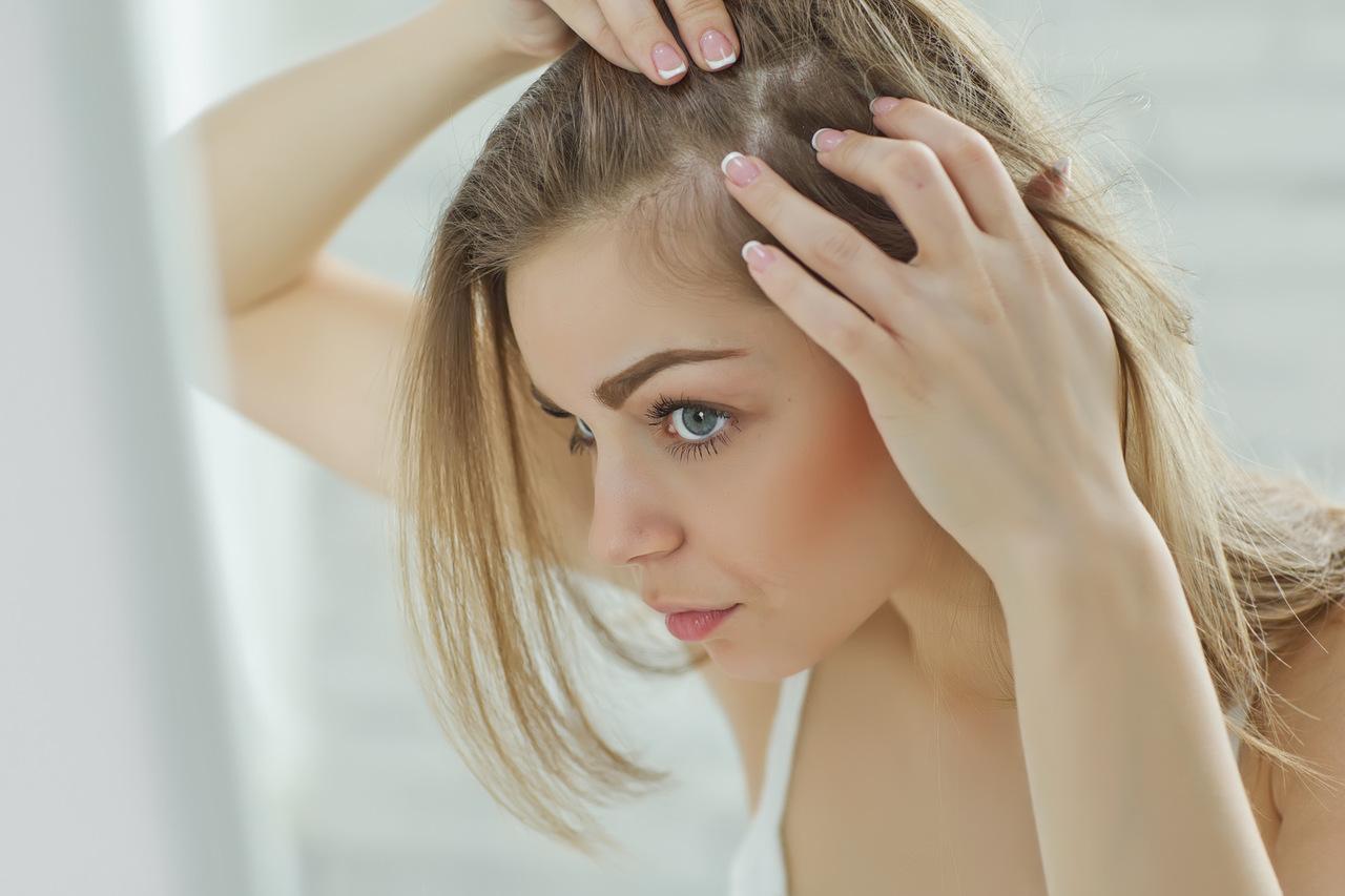 aynada saç derisini inceleyen sarışın kadın