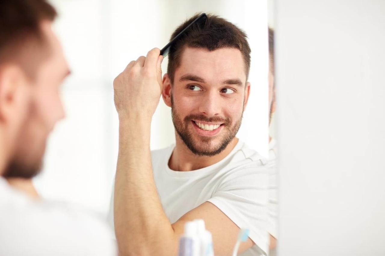 Aynada gür saçlarını tarayan mutlu adam
