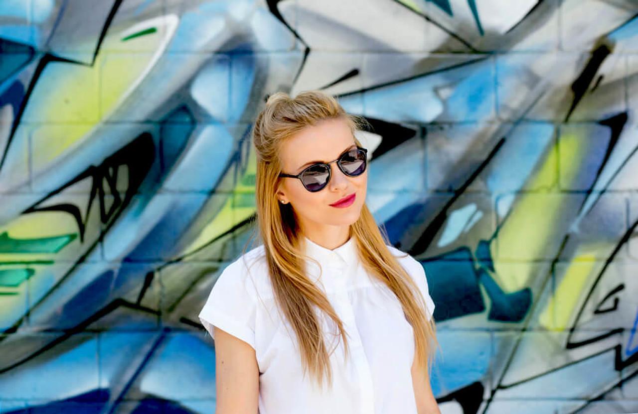 Yarım topuzlu saçları ile graffiti yapılmış duvarın önünde poz veren güneş gözlüklü sarışın kadın
