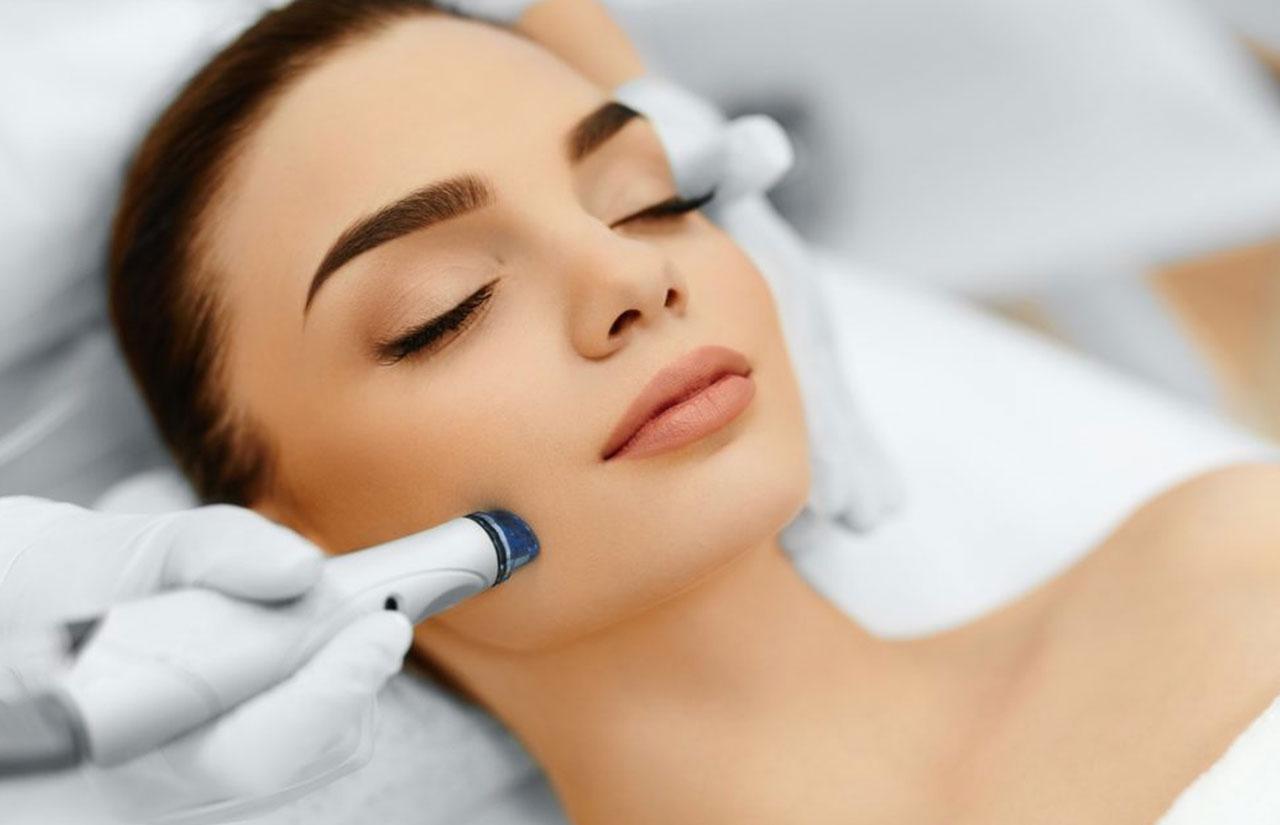Makyajlı bir kadın ve yüzünde hydrafacial cihazı