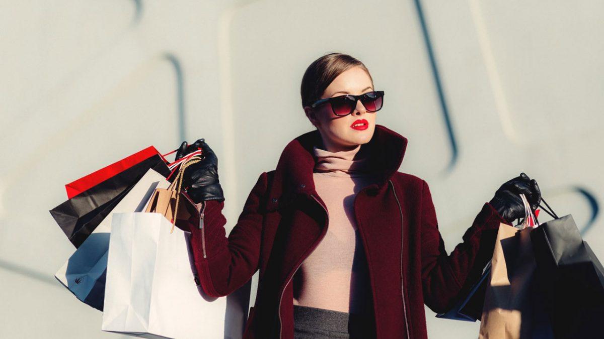 Kırmızı montlu bir kadın ve alışveriş çantaları