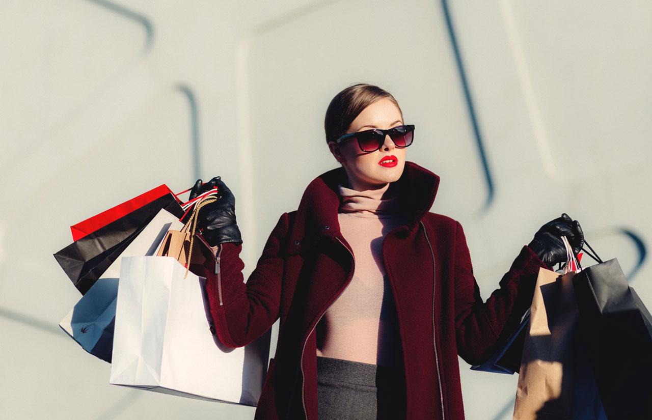 Kırmızı montlu bir kadın ve elinde alışveriş çantaları