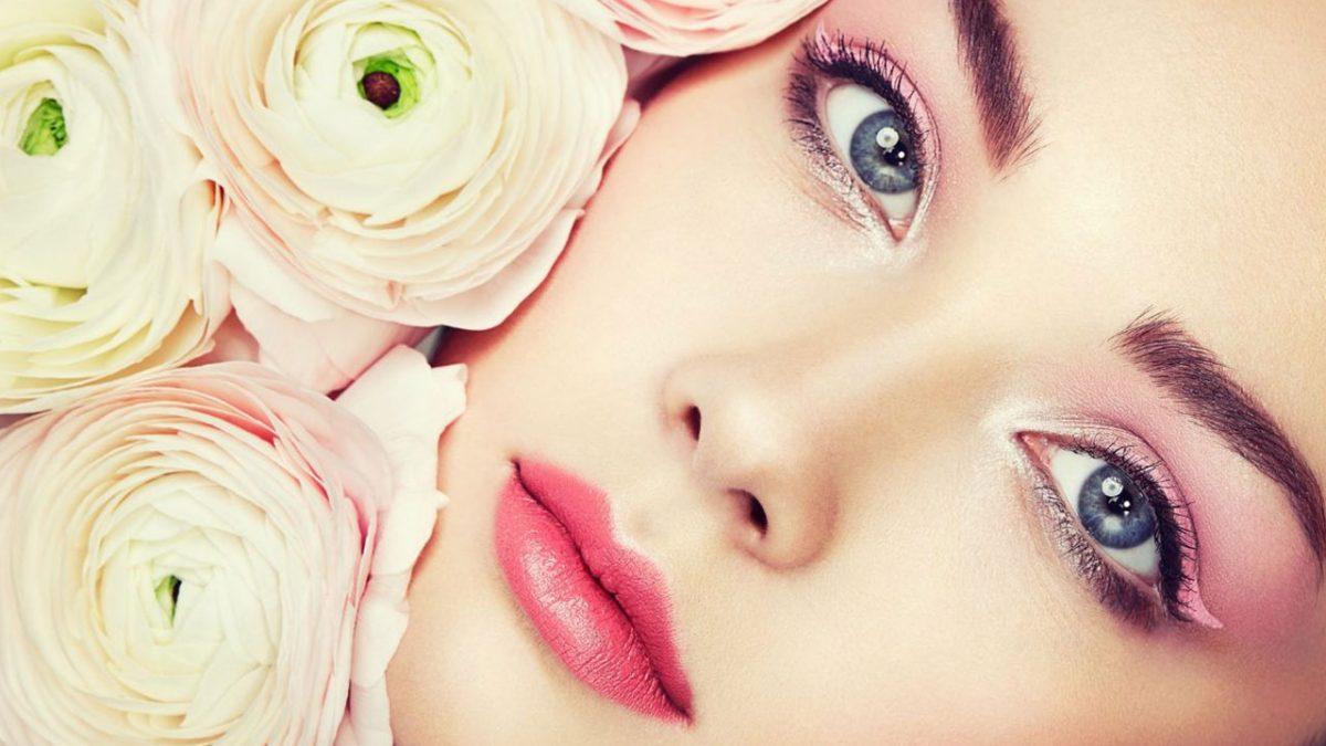 Makyajlı bir kadın yüzü ve yanında beyaz güller