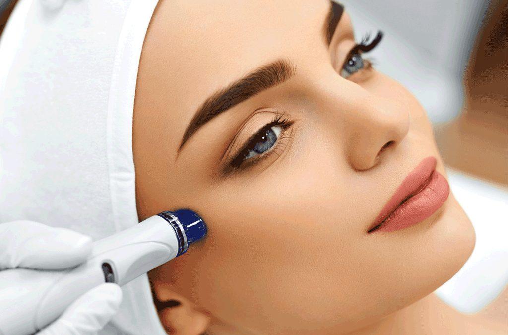 gülen mavi gözlü bir kadına hydra facial uygulaması yapılıyor