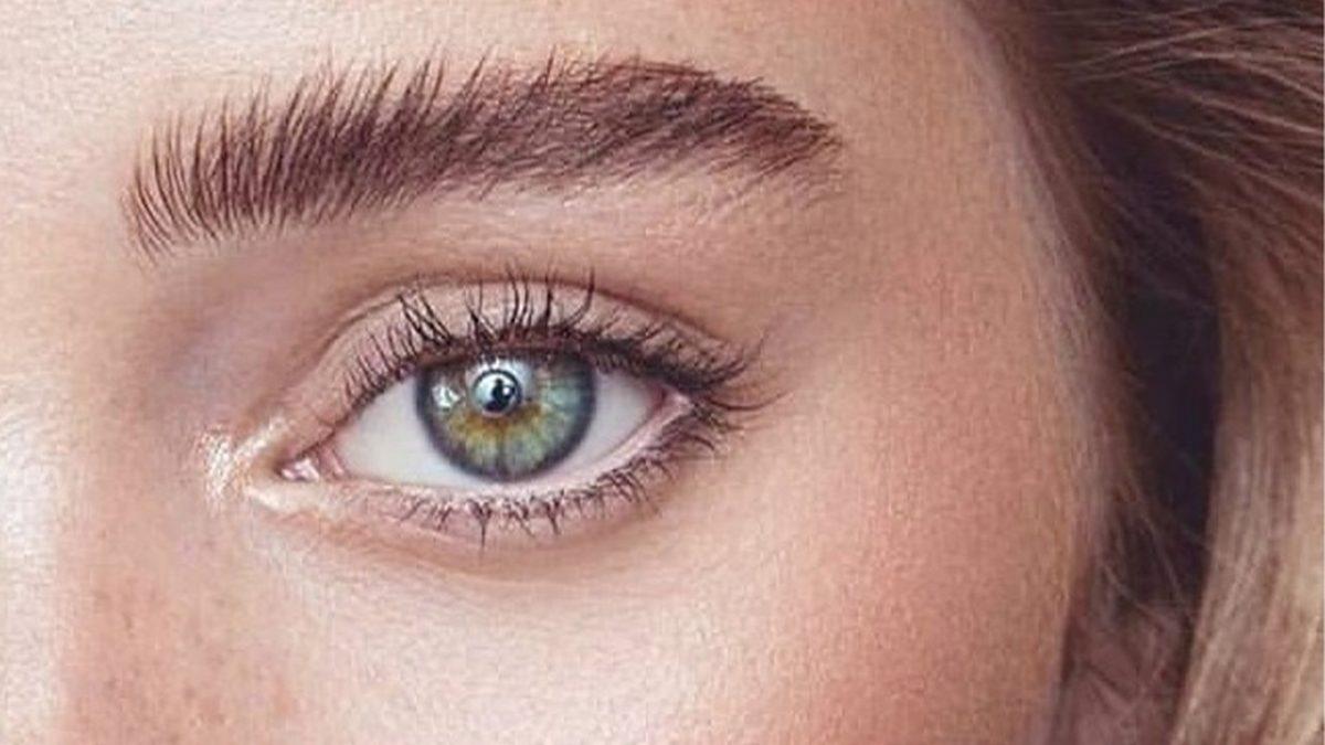 Kaş laminasyonu yaptırmış bir kadının yeşil sol gözü ile kaşlarının göründüğü bir fotoğraf kesiti