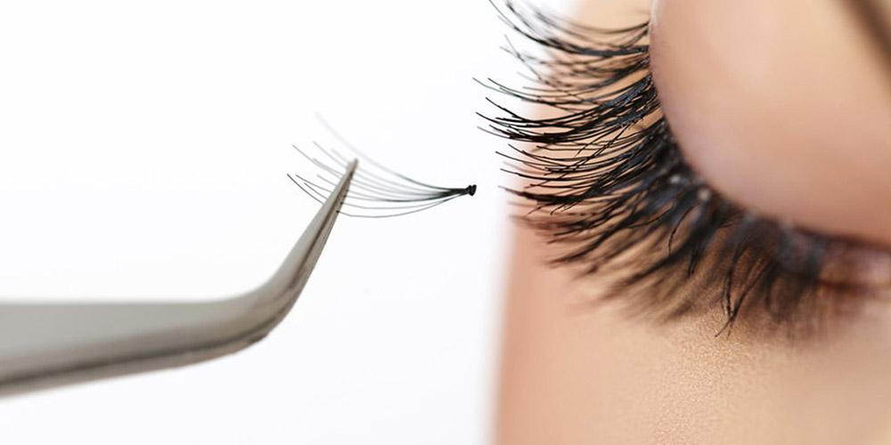 cımbız ucunda takılan ipek kirpik ve gözü kapalı bir kadının kirpikleri