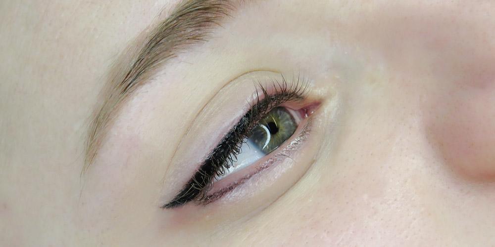 Yeşil gözlü bir kadın ve eyeliner uygulanmış olan sağ gözü