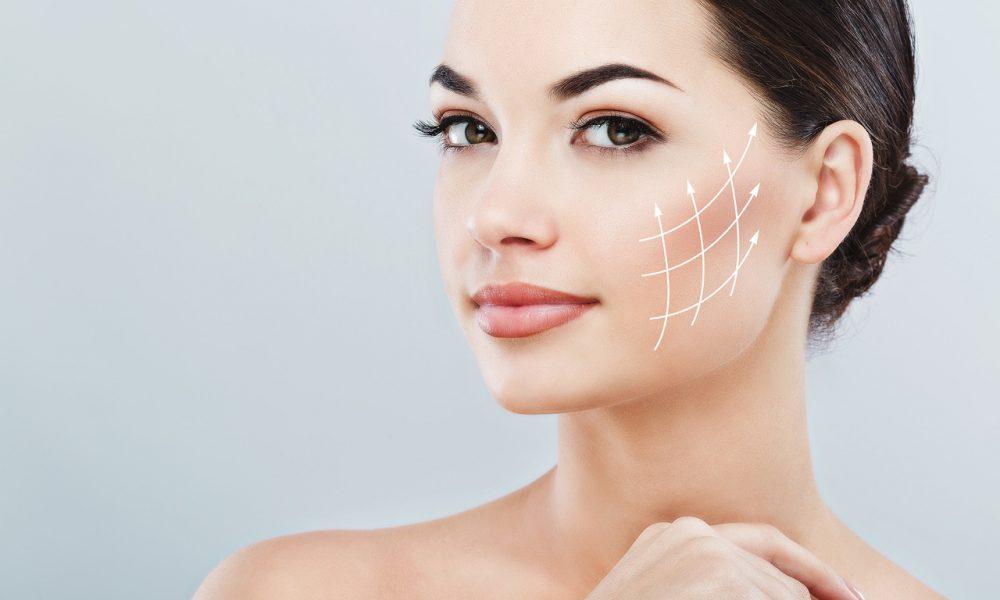 saçları toplu genç bir kadının yanağı üzerinde kırışıklıkları gidermeyi mümkün kılan anti aging etkilerini gösteren çizgiler