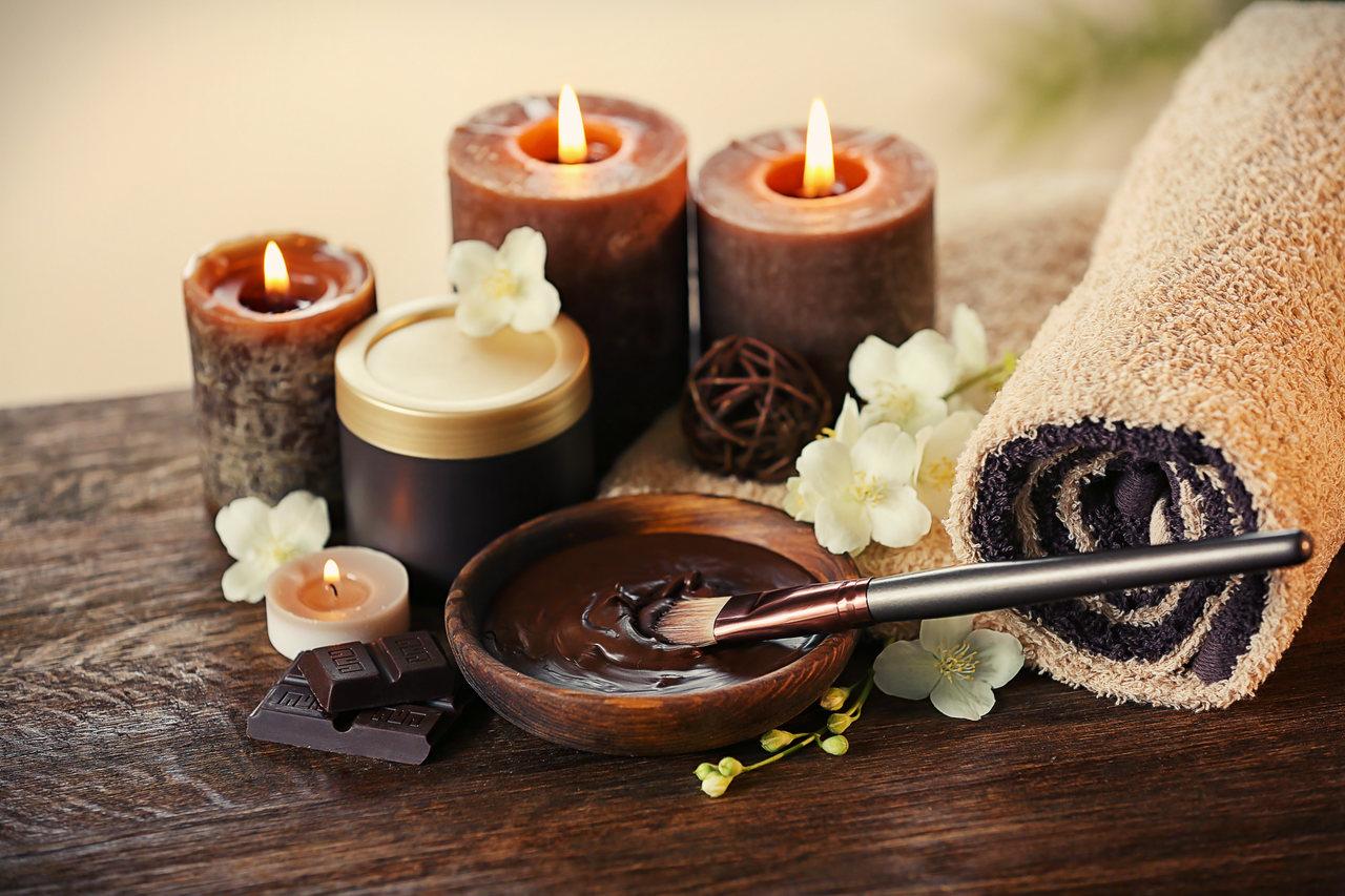 Ahşap bir masa üzerinde duran rulo havlu ile yanında ahşap bir kase içinde erimiş çikolataya batırılmış fırça ve arkalarında görünen mumlar