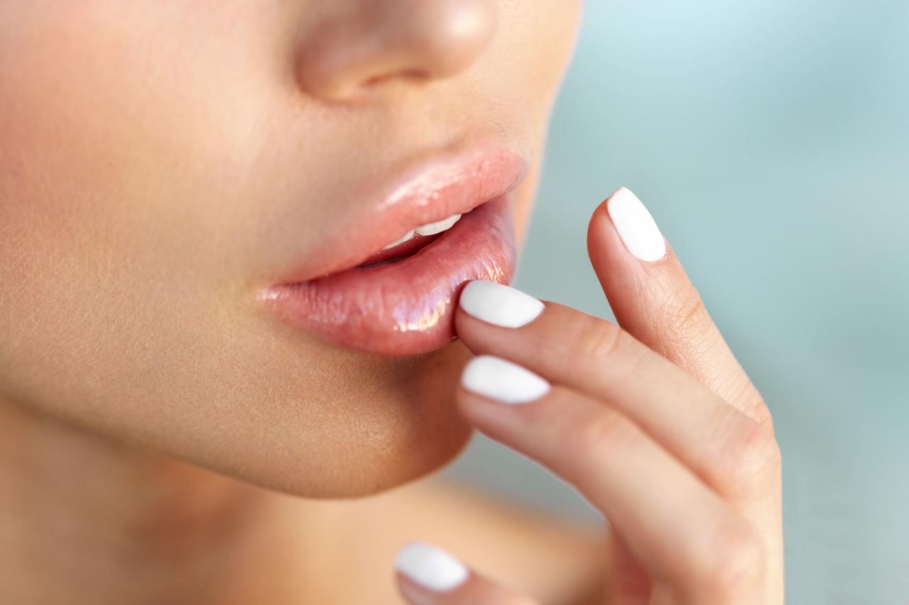 parmak uçlarıyla dudaklarına dokunan kadın