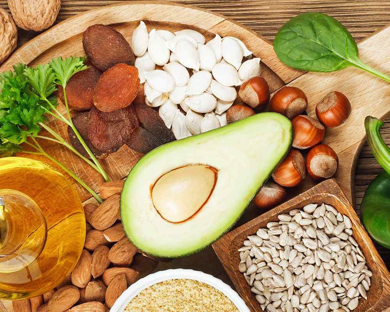 ahşap bir servis tabağının üzerine konmuş fındık, kuru kayısı, avokado, zeytinyağı, kabak çekirdeği, maydanoz gibi saç için vitamin e içeren besinler