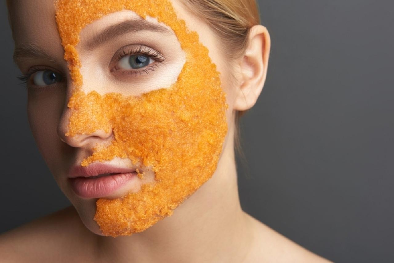 yüzünün yarısına turuncu bir maske uygulamış kadın