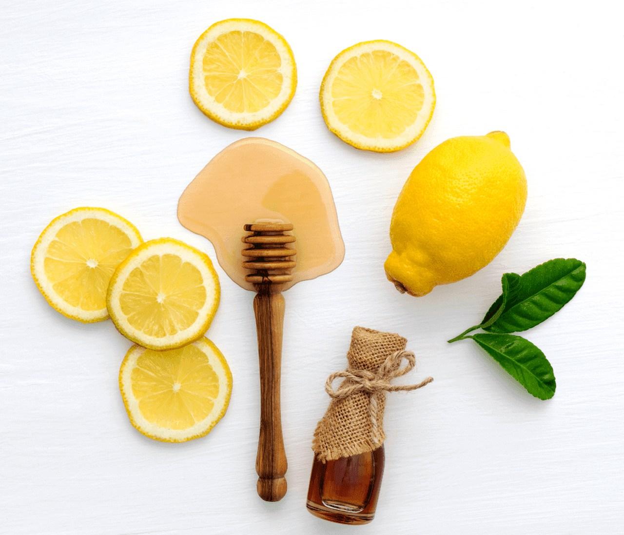 Yuvarlak limon dilimleri ile bütün halde bir limon ve yanlarında yatay bir şekilde duran bal kavanozu ile yüzeye damlatılmış bir miktar bal