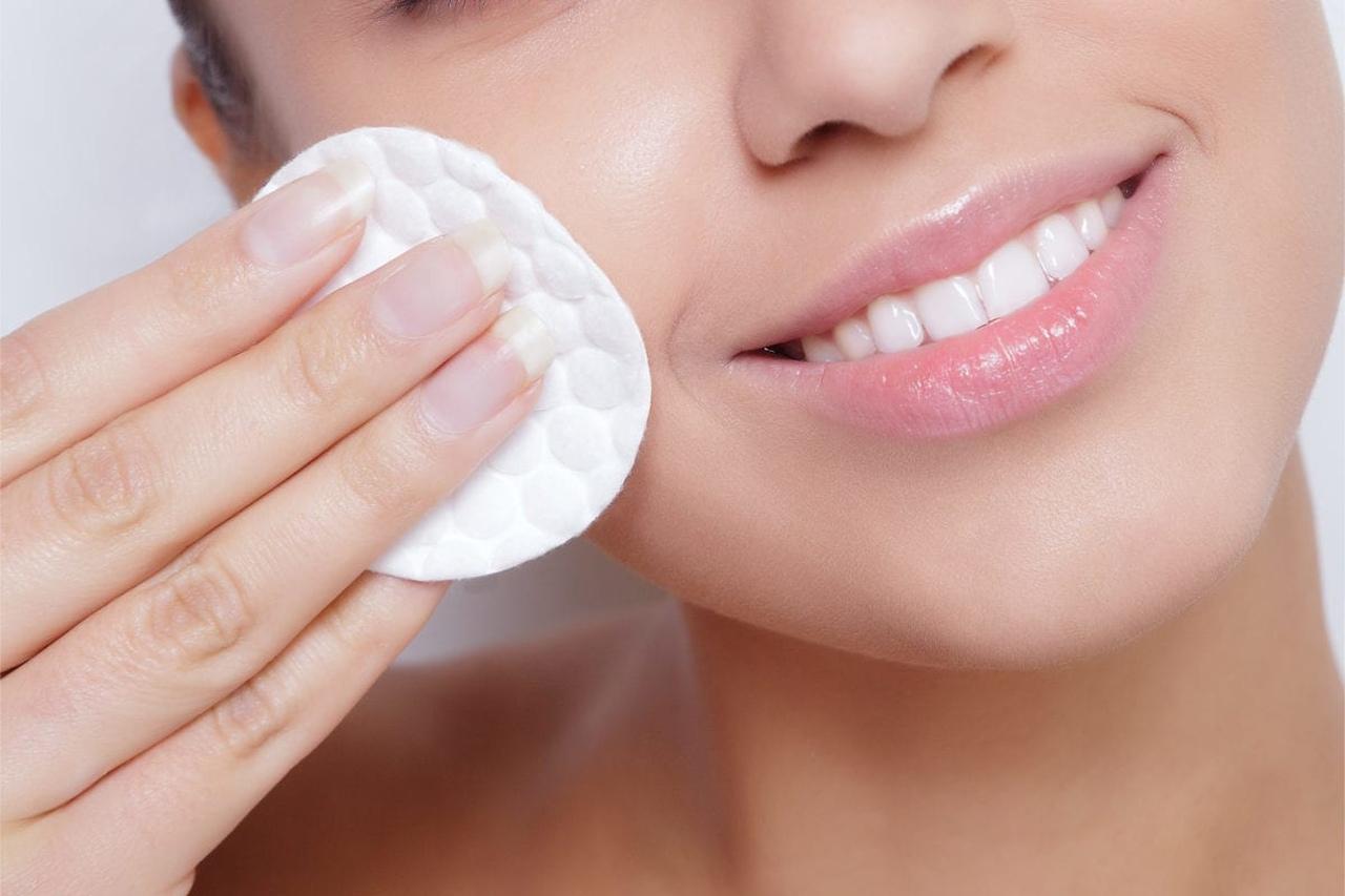 bir pamuk yardımıyla makyajını temizlerken gülümseyen kadın