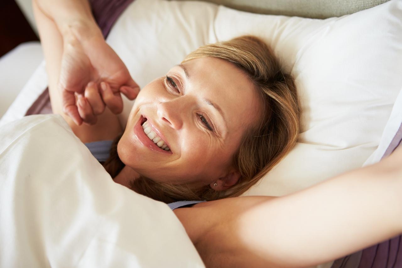 Yatağı içinde gerinen ve uykusundan gülümseyerek uyanan kadın