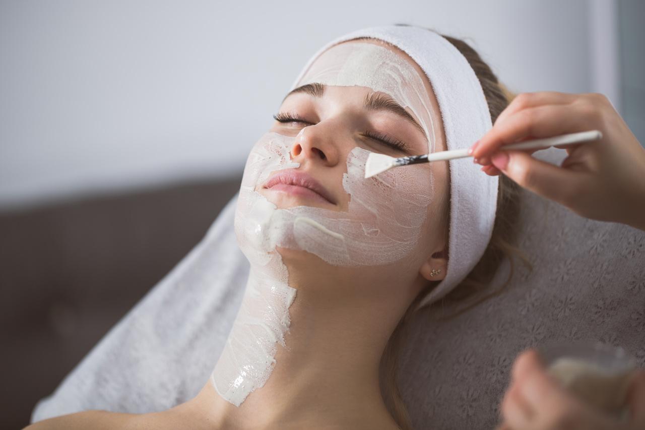 Güzellik merkezinde yüzüne peeling maskesi uygulanan kadın