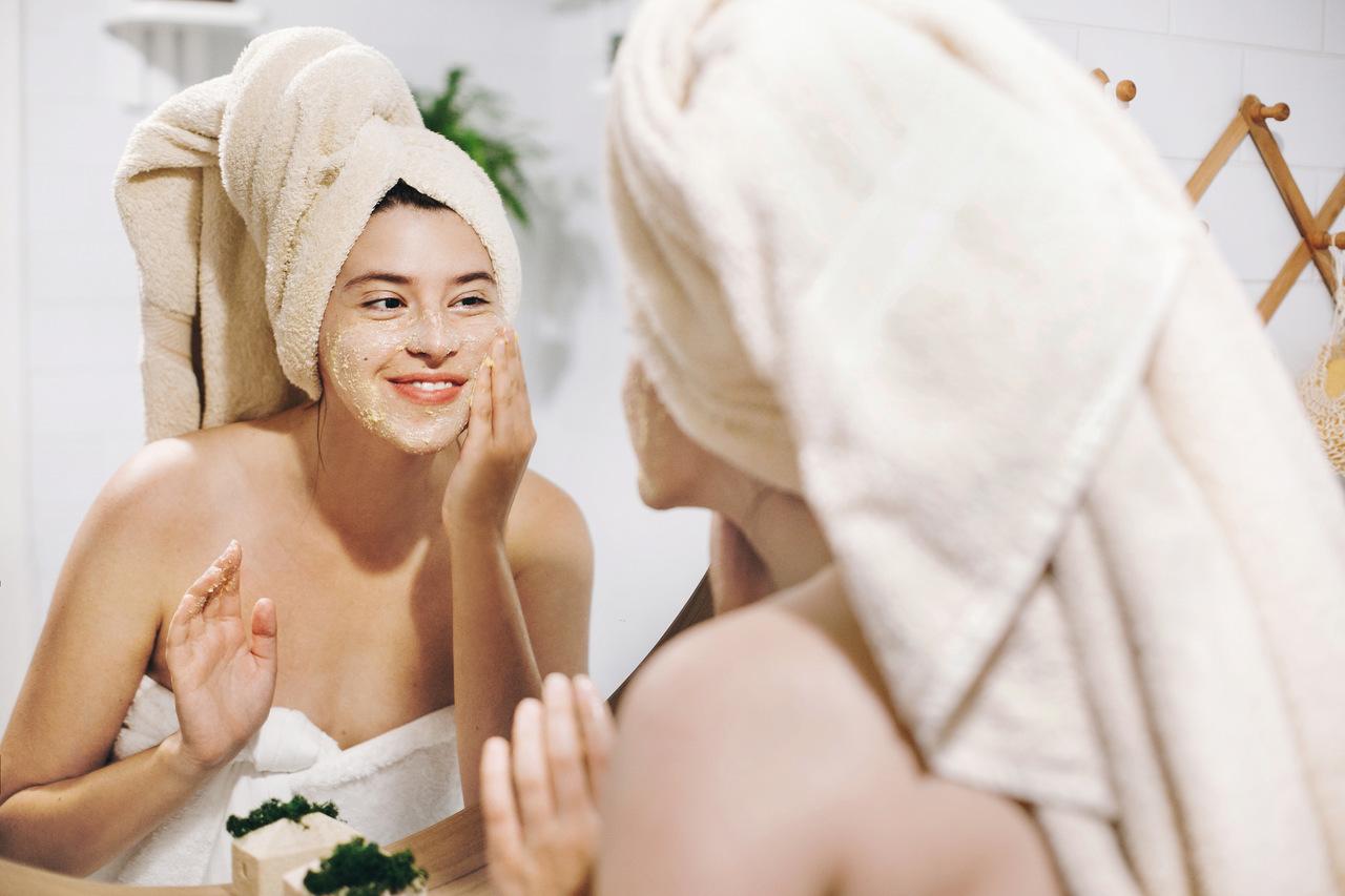 Aynada kendisine bakaran yüzüne peeling uygulayarak peeling nedir sorusuna yanıt oluşturan vücudunu havluyla sarmış kadın