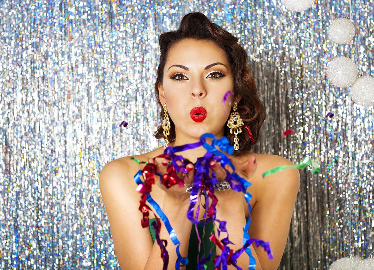 elinde renkli parti süsleri tutarak objektife öpücük atan makyajlı güzel kadın