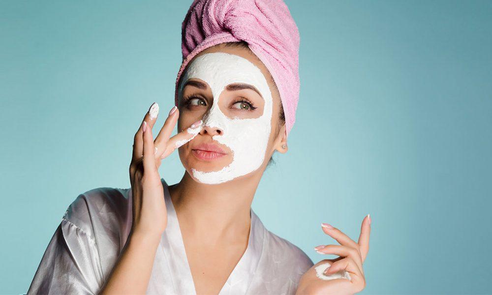 yüz bakımı için yüzüne nem maskesi uygulayan ve saçlarını pembe havlu ile sıkıca bağlamış sabahlık giyen kadın
