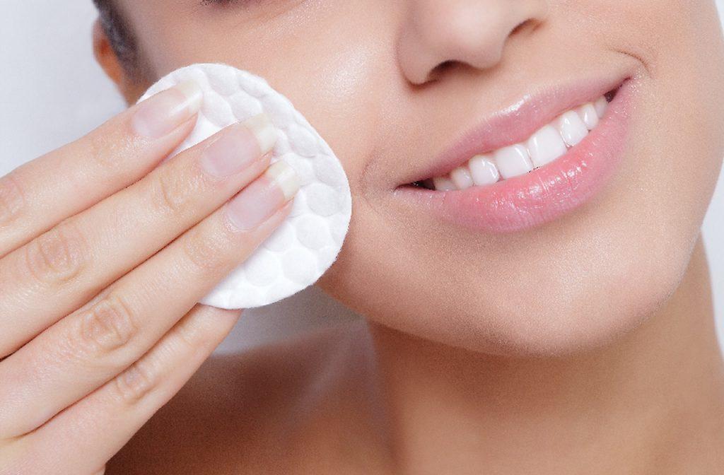 beyaz bir pamuk yardımıyla cildindeki makyajı temizlerken gülümseyen kadın