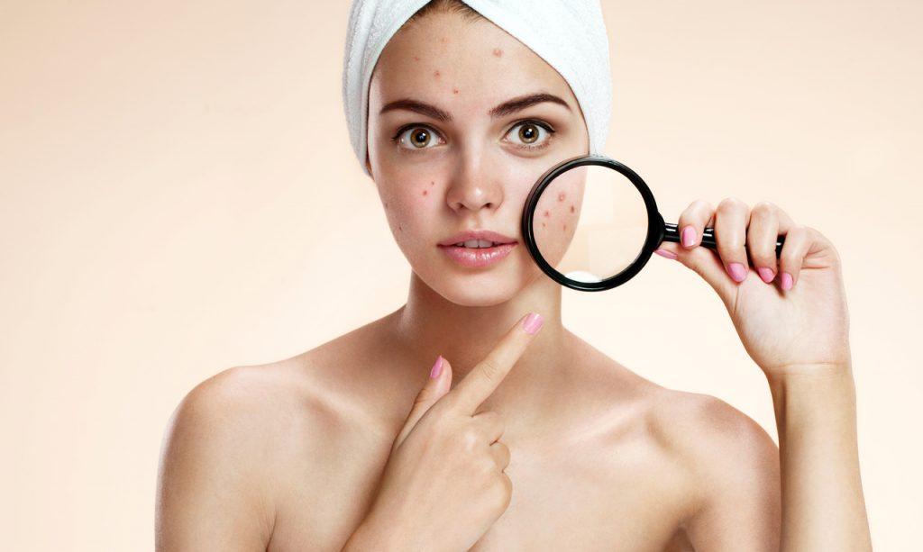 sorunlu cildine büyüteç tutan kaygılı kadın