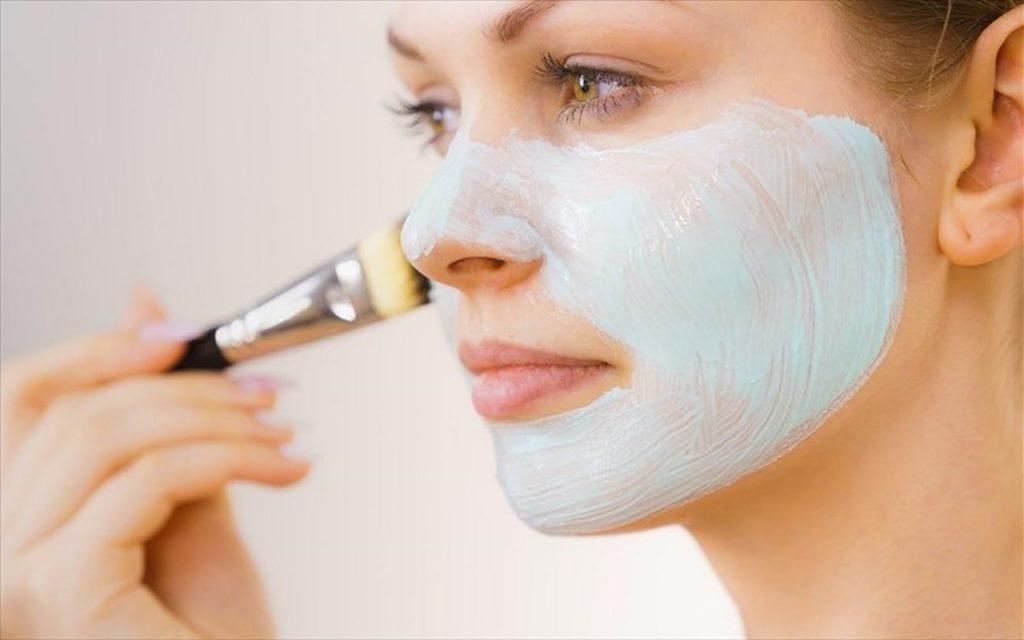 Yüzüne fırça aracılığıyla bakım maskesi uygulayan kadın
