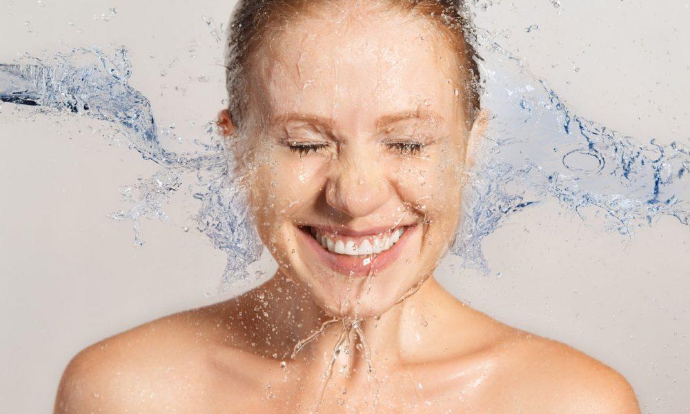Yüzüne su çarparken gülümseyen kadın