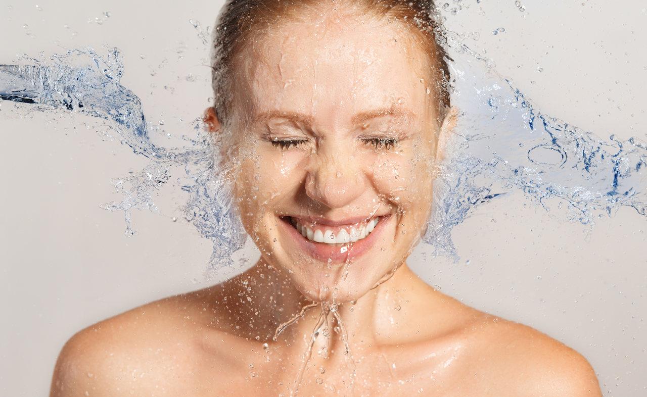 Cilt temizliği sırasında yüzüne su çarparken gülümseyen kadın
