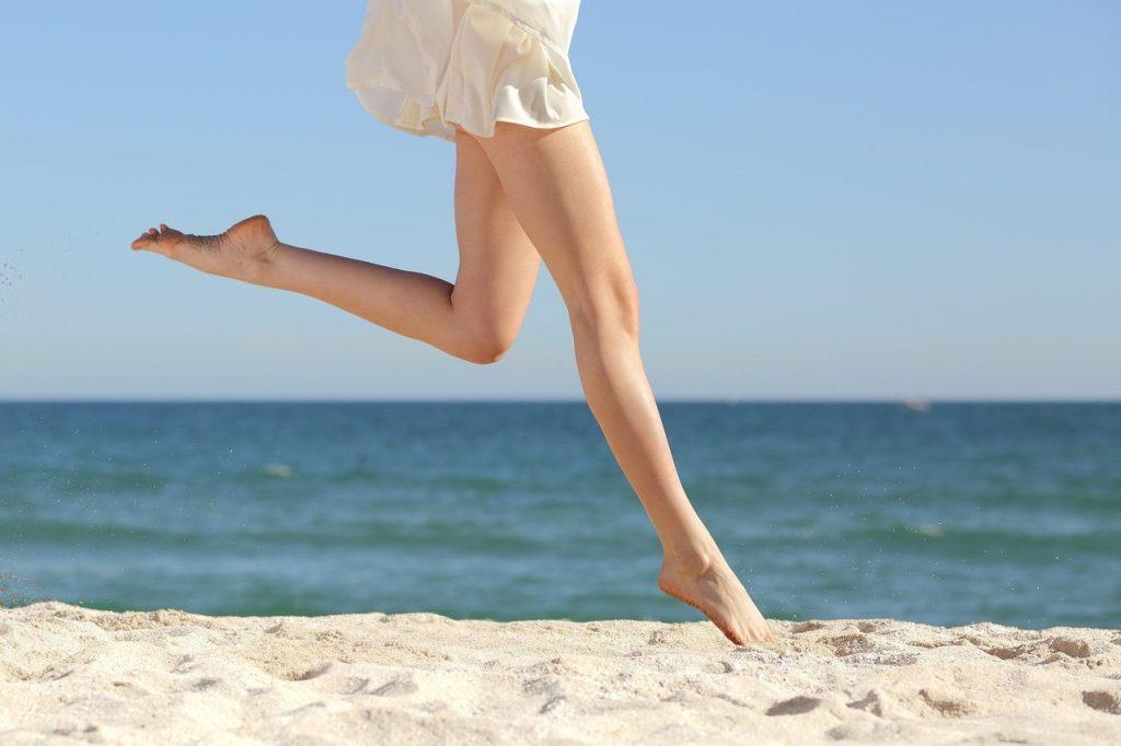 deniz kenarında kumsalda zıplayan kadının bacaklarının görüntüsü