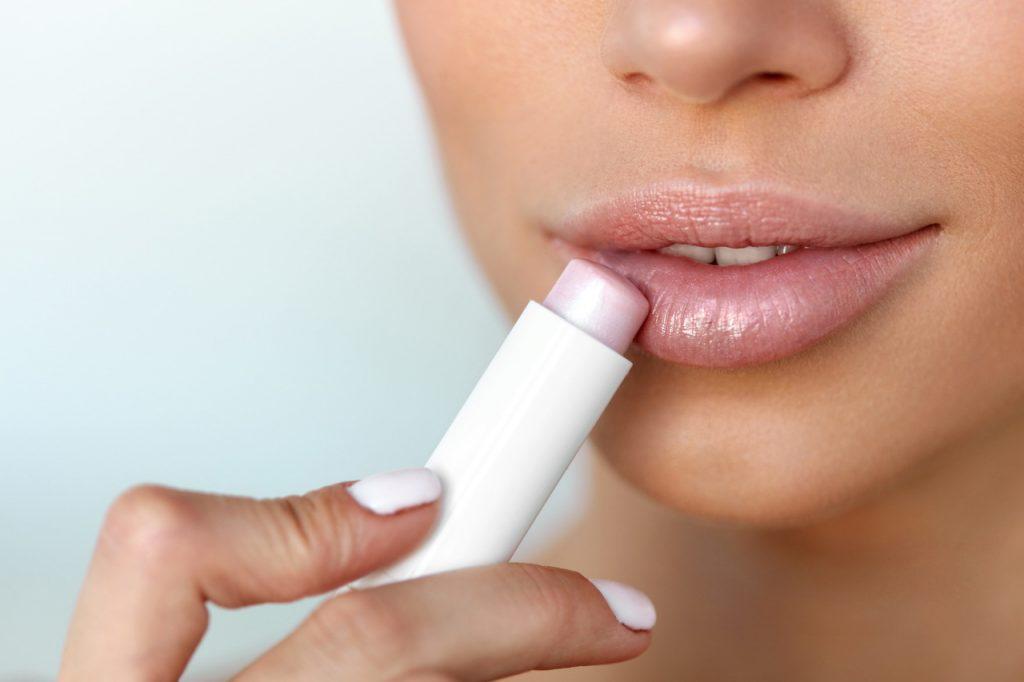 Dudak balmı süren kadının dudakları