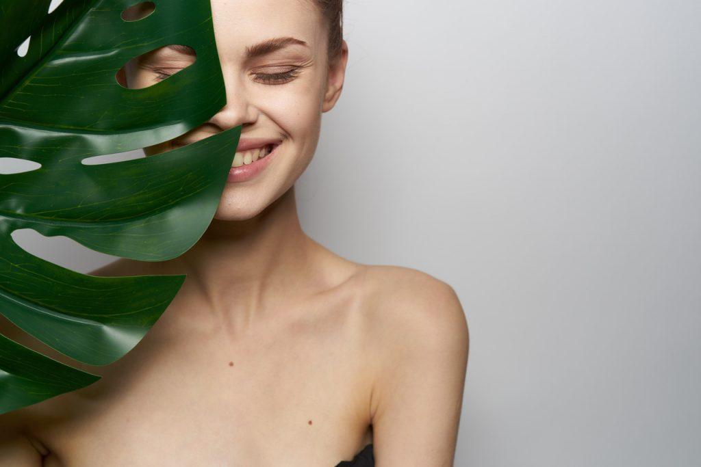 Geniş ve büyük bir yaprağın arkasından yüzünün yarısı görünen mutlu kadın