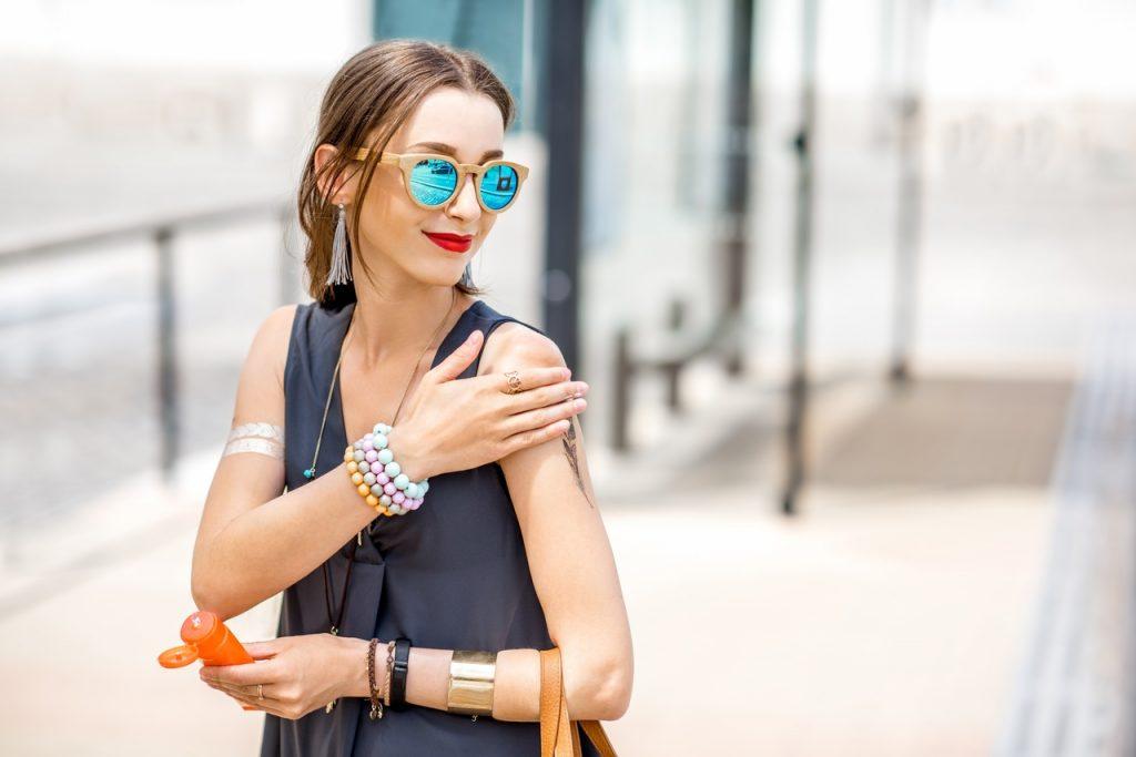 Dışarıda gezerken omuzlarına güneş koruyucu süren güneş gözlüklü kadın