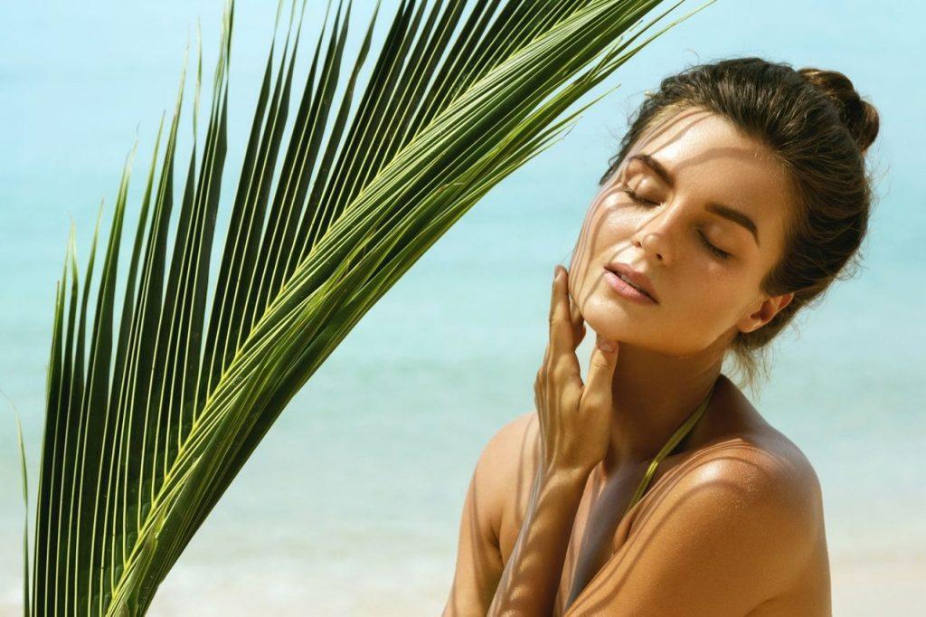 Palmiye ağacı gölgesinde duran ve yüzüne dokunan gözleri kapalı kadın