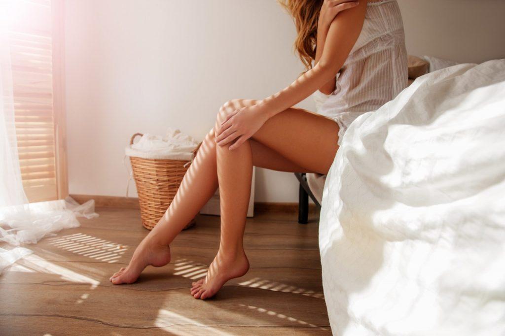 Yatağında oturarak pürüzsüz bacaklarına dokunan kadın