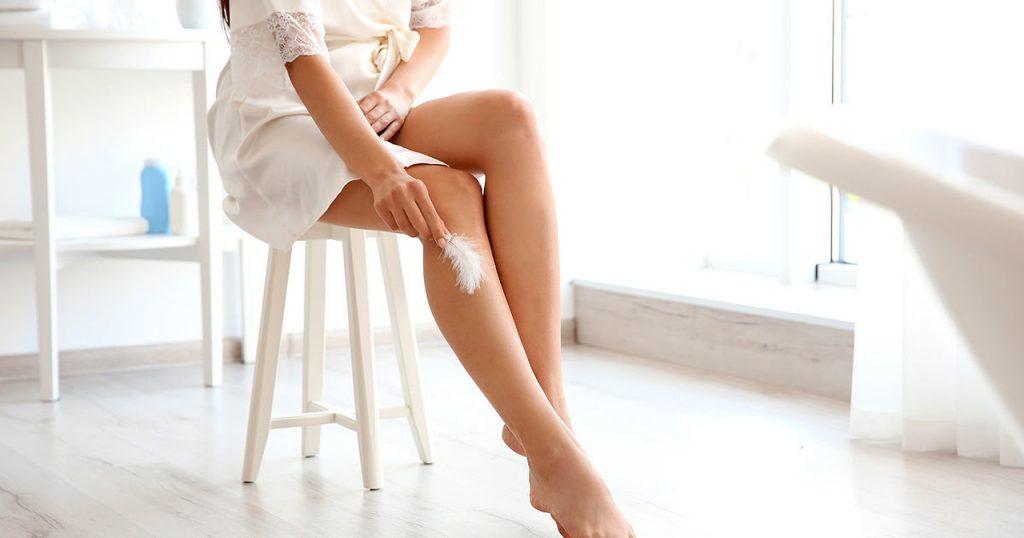 Taburede oturan ve pürüzsüz bacaklarına kuş tüyü ile dokunan kadın